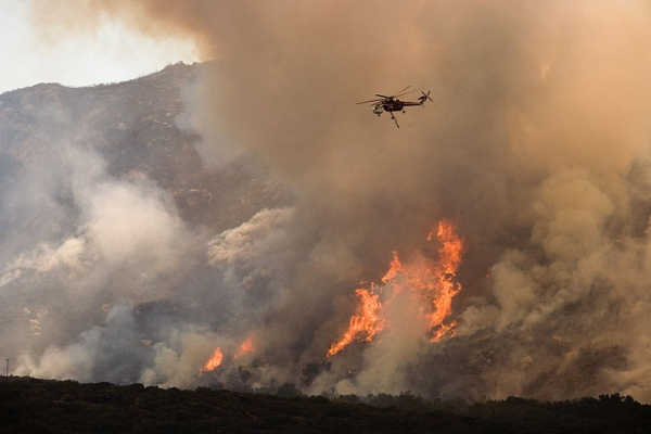 A helicopter drops water on a wildfire in California, Oct 2007 (photo by FEMA via Wikimedia Commons)